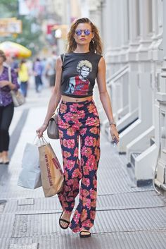 Behati Prinsloo wears a rock n roll cropped tank, floral Reformation pants, sandals, and mirrored sunglasses Behati Prinsloo, Looks Style, Style Me, Modell Street-style, Look Boho, Floral Pants, Fashion Week, Dame, Oakley