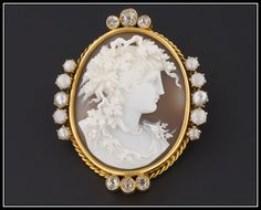 This miniature masterpiece (circa 1870-1890) depicts the head and shoulders profile of a bacchante with grape vines in her hair and donning a bead necklace and gossamer gown. The carving of the shell cameo is done in high relief with pierced work vines accenting the bacchante's hair.  An equally beautiful mount accents this tiny treasure. The mount is fashioned of 14k yellow gold, old mine cut diamonds, and pearls. | via Trademarkantiques on Etsy