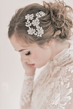 A flower hair piece provides a balance to a somewhat simple and messy bun. Its design complements the dress style. It is recommended to be medium-sized so as not to cover the whole side but enough to draw attention.