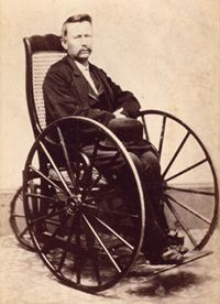 1800s photo portrays large wooden wheels and absence of push rim
