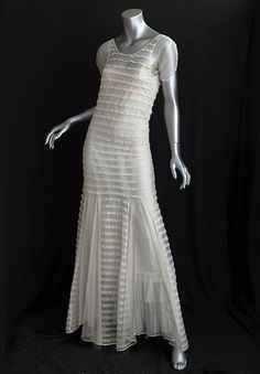 Cotton tulle summer evening dress, 1930s  This romantic dress was made from ivory cotton tulle embellished with rows of horizontal tucks. The torso of the dress clings to the body like a second skin. The skirt is flared below the hipline with bias-cut panels. The sleeves are open on top of the arms..