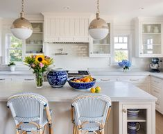 U-shape kitchen in a cottage style home features a gray center island with glass display cabinets flank blue bistro counter stools. Beach Theme Kitchen, Nautical Kitchen, Kitchen Decor, Kitchen Ideas, Condo Kitchen, Kitchen Designs Photos, New Kitchen Designs, Design Kitchen, Beach House Kitchens