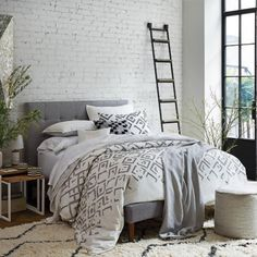 Confortável, a cama foi responsável por aquecer este quarto que, com luz natural abundante, apresenta um estilo industrial.