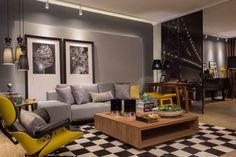 Escritório do Empresário. Alex Araujo experimentou uma paleta de cores urbana, representando as cidades em preto, branco e principalmente cinza. O amarelo é adicionado de forma pontual e irreverente, em peças de design. O tapete quadriculado é um destaque, assim como as molduras que descentralizam as fotografias em preto e branco.