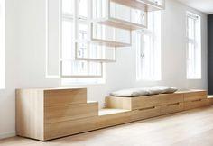 La scala sospesa termina sulla panca-divano che corre lungo la facciata anteriore del loft e che incorpora dei pratici cassetti. Design Haptic Architects