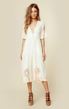 This dreamy little number by Cleobella is adorned with scalloped trimmed sleeves and cropped bottoms that are delicately hand embroidered. Features a deep v neckline with accented buttons.  Made in In