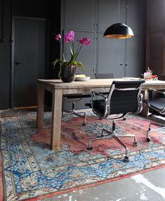Grote houten tafel met fantastisch kleed en zwarte inbouw kasten. Kantoor en atelier in een lampenkappen fabriek - Makeithome.nl
