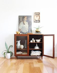low wood cabinet with glass doors and portrait painting / sfgirlbybay