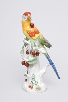 An animal figurine Parrot with cherries Meissen, 20th cent. Parrot seated on a big branch base ecorated with applied leaves and cherries. Crossed swords in uglaze blue with 1 incision line. impr. 64895, inscr. 5. Min rest. H. 32 cm.