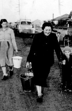 29 July 1953: In Sunshine where the roads were unpaved and there was no running water, Mrs Anita Steigler and her son Ernst along with the family dog set out for home with a bucket of water.