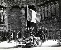A French woman surrounded by Parisian police waves the French tricolor flag in tribute to General Leclerc's 2nd Armored Division (French: 2e Division Blindée, 2e DB) as they march past Notre Dame Cathedral. The French 2nd Armored Division, along with...