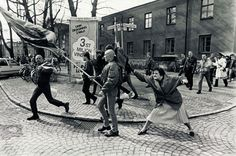 Växsjö, Sweden, 1985. Nazis are marching through the streets. Out comes an old lady and hits a nazi in the head. Photo by Hans Runesson.