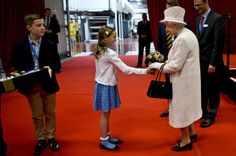 Queen Elizabeth II is given a posie of flowers by Jessica Barrell, 9, from Gilwern Primary School following a visit to International Greetings UK Ltd at the Penallta Industrial Estate in Ystrad Mynach during her visit to south west Wales on April 30, 2014