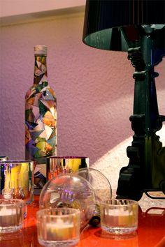 outro Subwoofer, este em laca com brilho na cor vermelho, serve de mesa de apoio ao lado do sofá, a garrafa de Sagatiba foi estilizada pela artista Goiana  Rosi Rosa