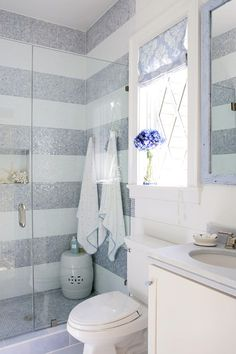 Horizontal stripes in silver and white tile bring so much style to this bathroom! Live this idea!