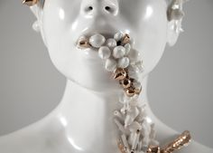 Jess Riva Cooper (previously) produces smooth ceramic busts, the mouths agape rather than closed in smile or silent contemplation. Tangled vines and rosebuds sprout from their mouths, and in some cases leaves from plants pop from the busts' noses, engulfing the faces in their entirety. In each bust