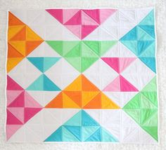 ❤︎ This item is made to order ❤︎ This quilt takes 2-3 weeks production   This modern baby quilt, the-->> R A E <<-- quilt is carefully handcrafted with 100% cotton quilting grade fabric in a bright modern color scheme that will appeal to a babys eye. The colors in the modern baby quilt top consist of, White, Pink, Green, Teal, & Orange. The backing is made of the same 100% cotton in a bright pink tribal pattern that ties in the geometric shapes from the quilt top. The quilt b...