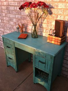 A thrift store desk that had a broken drawer and peeling veneer and crap stuck to desktop was transformed with CeCe Caldwell paint in Santa Fe Turquoise and heavily distressed and waxed.  The pulls were perfect!  I decided to ditch having a new drawer front made and used an old wire basket for visual interest!  I love it!