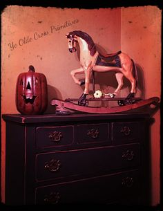 Antique pull horse Rockinghorse sitting on top of a old dresser I re did. Dressed for autumn by Ye Olde Crow Primitives.