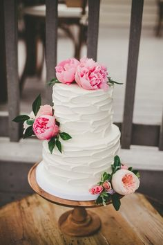 Delicious looking white wedding cake with soft pink peonies and Juliet roses.