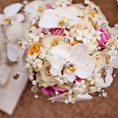 Pink and white bouquet of orchids, stephanotis, roses, and calla lilies that were accented with crystals.