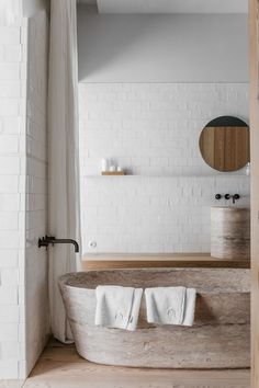 A rustic luxe bathroom at Santa Clara 1728 by João Rodrigues and Manuel Aires Mateus. Stone bath white walls black faucet