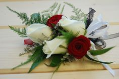 A white & Red rose corsage with a wisp of plumosa & Italian ruscus.