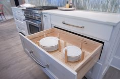 Dish storage drawer with pegs Design by Dalton Carpet One Wellborn Cabinets- Finish: Back Wall - Maple Glacier; Island - Willow Door Style: Messina Countertops: Caesarstone Fresh Concrete; Calcutta Latte Floor Tile: Logwood Grey Grout: Mapei Pewter Photo by: Dennis McDaniel