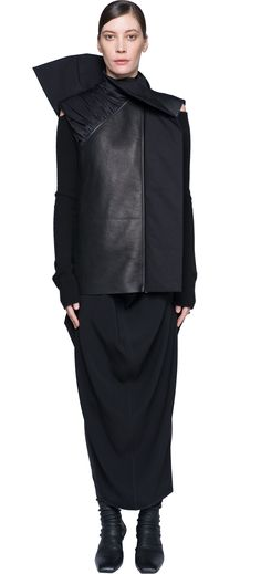 Rick Owens defines himself as an uncompromising designer. He choose to be extreme in his creativity! He gives shapes and manipulates them to create something that you'll never seen before. This black jacket for woman, for example, reflects the spirit of Rick Owens's style. Special cut, sleeveless, draping detail behind on the shoulder, an off-center closure. Really fashion for all women who love to be trend!