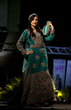 In this photo taken Thursday, May 1, 2014, a model displays a blend of traditional Palestinian embroidery and modern designs in a creation by designer Intisa...