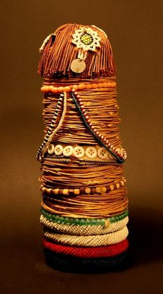Africa | 'Gymwane' dolls from the Ntwane people of South Africa | Built around a core of slightly tapered wood, covered with braided plant fiber rings, the doll is decorated with beads, buttons, pieces, and various other items | From the former collection Udo Horstmann