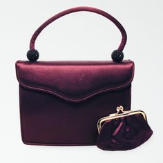 This classic Judith Leiber evening bag features a beautiful plum-coloured satin exterior, trimmed with black sequin accents along the handle ends. ...