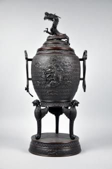 A most outstanding large Japanese bronze temple Koro, having superb all over decoration, with central panel of embossed dragon and phoenix mounted with a dragon to the top. Meiji period. Height 64 cm