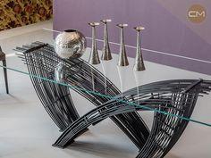 Mesa transparente con base de acero, diseñada por Giorgio Cattelan. ¡Búscala en Corso Moliere!
