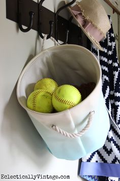 What a great idea - hang a HomeGoods canvas basket from a coat rack - instant storage for sunglasses, sunscreen or softballs!  Love this mudroom! #HomeGoodsHappy #HappybyDesign #sponsored eclecticallyvintage.com
