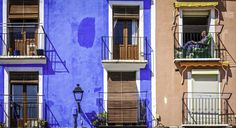 A place to read - A man relaxes on a small balcony in Villajoyosa, Costa Blanca, Spain, with two dogs and a book. The distinctive, brightly coloured, buildings were oringinal so that sailers returning home could see their houses