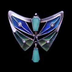 This is not contemporary - image from a gallery of vintage and/or antique objects. JUGENDSTIL BROOCH  A silver, winged shaped, blue & green plique-a-jour brooch set with pearls and with a central chrysoprase stone and chrysoprase drop.