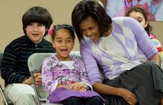 Michelle Obama's argyle pastel-colored cardigan sweater softens up her charcoal pleated skirt.