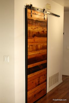 DIY sliding wood door.  It'd be awesome to find an old barn door to reuse for this.