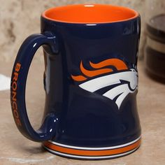 Denver Broncos 15 Ounce Sculpted Logo Relief Coffee Mug by Boelter. $14.99. For the truly devoted fan, we are proud to present this officially licensed Denver Broncos coffee mug from Boelter Brands. Now you can brighten up your office or home with your favorite NFL team's colors and logo while you enjoy your favorite beverage. The 15-ounce ceramic mug features a 3-D sculpted relief logo on each side, plus the team name printed on the handle. Perfect for coffee, tea, or...
