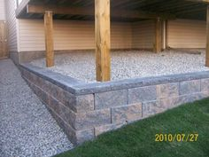 This small wall was added to eliminate having a slope that would be difficult to mow. It also allowed the homeowner to hide the concrete pillars and cardboard tubes from the deck construction. Picture compliments of Dream-yard.