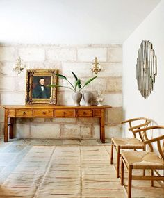 7 Bad Décor Shopping Habits to Stop Right Now// Open foyer with Wishbone Chairs, portrait, and stone walls