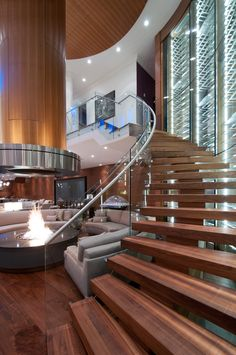 Curved staircase around indoor firepit with a 3000 bottle glass encased wine cellar in West Vancouver #blurrdMEDIA #architecture #photography