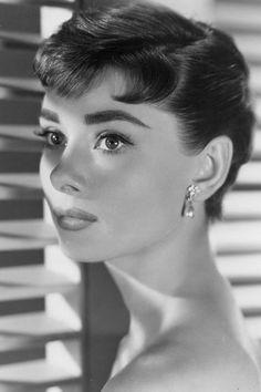 Audrey Hepburn, le style mythique d'une icône. Les bijoux délicats: Audrey Hepburn ne mettait jamais de montre à son poignet et ne portait pas plus d'un bijou à la fois. Elle choisissait des parures fines, comme ces boucles d'oreilles en perle, dans Sabrina, en 1954.