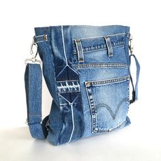 """A functional design makes this convertible laptop backpack/cross body bag perfect for anyone on the go. I made it from a retired denim pant.This backpack has two outside pockets.One of these pockets is 12""""x 8.5"""", and fits any tablet that is not wider than 8.5"""". I lined it with a dark blue fabric ,and added two interior pockets.  The convertible strap allows you to convert from backpack to cross body. Both ends of the strap can be adjusted and attached to D-rings by high quality swivel cl..."""
