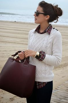 White cable knit sweater, red plaid button down shirt, brown bag, and gold accessories: