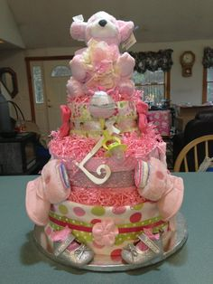 Diaper Cake for baby girl made with 125 diapers. Decorated with receiving blankets, ribbons, shoes, boots, socks, mittens, head bands, pacifier, diaper cover, crinkled paper, letter, and stuffed animal!