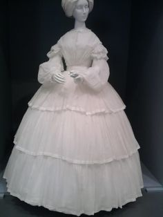 Sheer, European, ca 1855. Gathered high bodice, shown with a collar; bishop sleeves headed by 2 puffs and having a frill at the cuff; 3-flounced skirt. LACMA.
