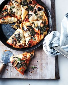 Skillet Pizza with Eggplant and Greens: The sauce and toppings can be prepared up to two days ahead. If you make only one pizza, freeze the other half of the dough in a resealable plastic bag for up to three months.
