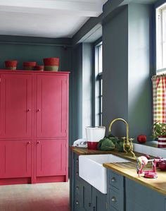 A bright red cupboard in this grey kitchen adds vibrancy to the scheme and draws together the red accessories in the room